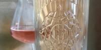 La bouteille sans étiquette indique évidemment les informations légales, mais elles sont reportées sur une petite contre-étiquette placée très bas, afin de ne pas paraître en transparence et laisser la vue porter sur la robe rose du vin, le blason UP et les élégantes rayures en relief du verre blanc.